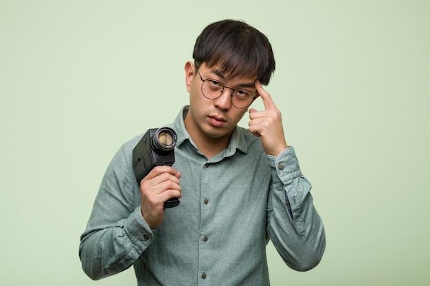 Junger chinesischer mann, der eine weinlesekamera denkt an eine idee hält