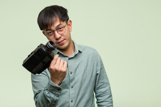 Junger chinesischer mann, der eine weinlesekamera einlädt zu kommen hält