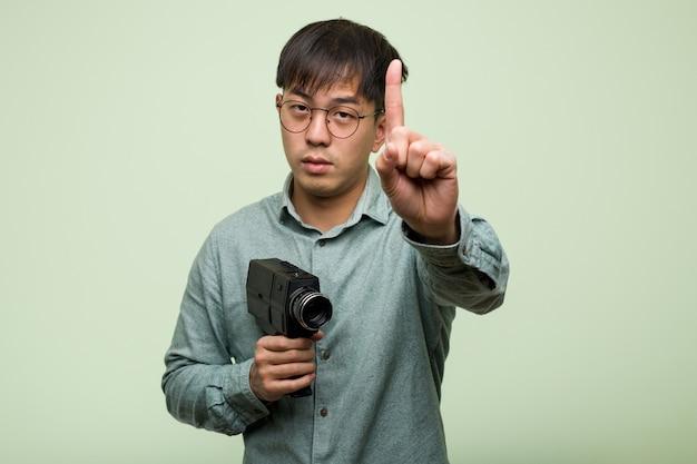Junger chinesischer mann, der eine weinlesekamera zeigt nummer eins hält