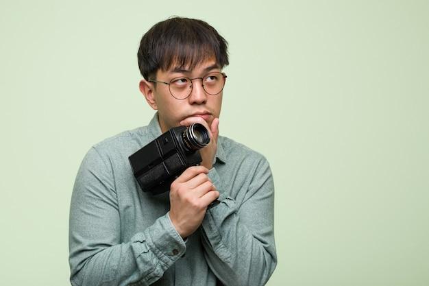 Junger chinesischer mann, der eine weinlesekamera zweifelhaft und verwirrt hält