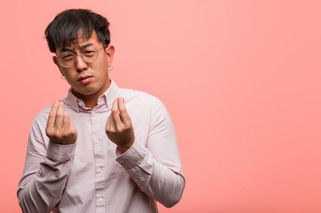Junger chinesischer mann, der einen gestenbedarf tut