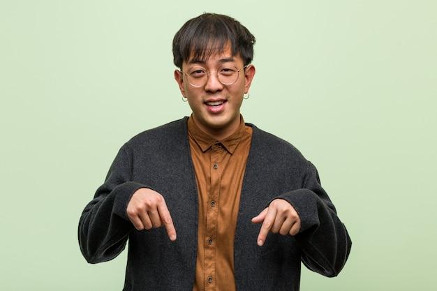 Junger chinesischer mann, der einen kühlen kleidungsstil gegen ein grün trägt