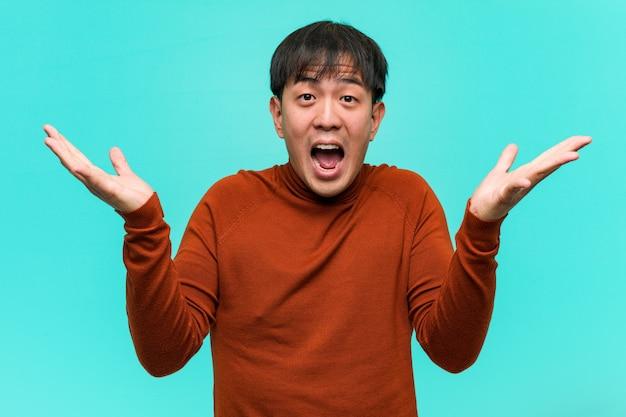 Junger chinesischer mann, der einen sieg oder einen erfolg feiert