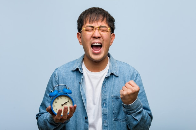 Junger chinesischer mann, der einen wecker überrascht und entsetzt hält
