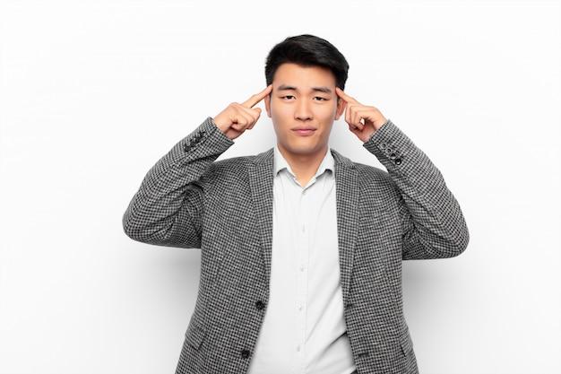 Junger chinesischer mann, der konzentriert schaut und über eine idee nachdenkt und sich eine lösung für eine herausforderung oder ein problem gegen flache farbwand vorstellt
