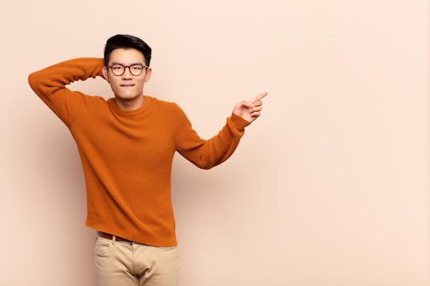 Junger chinesischer mann, der lacht, glücklich, positiv und überrascht aussieht und eine große idee verwirklicht, die auf seitlichen kopierraum gegen flache farbwand zeigt