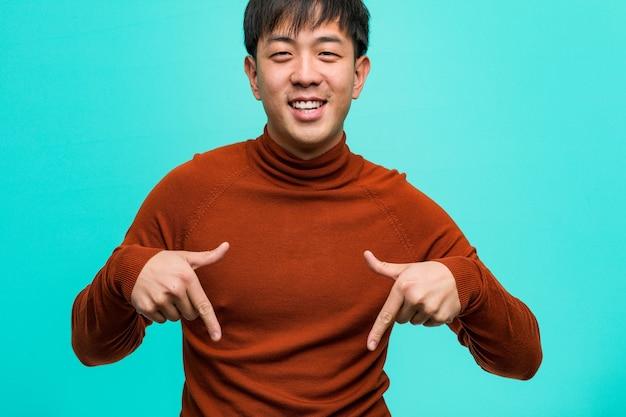 Junger chinesischer mann, der mit den fingern auf den boden zeigt