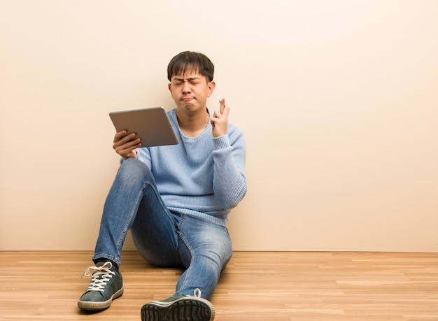 Junger chinesischer mann, der mit seiner tablette die finger kreuzend für glück hat sitzt