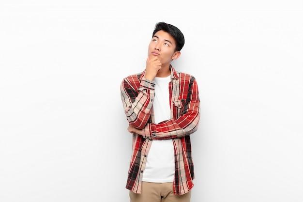 Junger chinesischer mann, der nachdenklich fühlt, ideen wundert oder sich vorstellt, tagträumen und nach oben schaut, um raum gegen flache farbwand zu kopieren