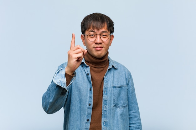 Junger chinesischer mann, der nummer eins zeigt
