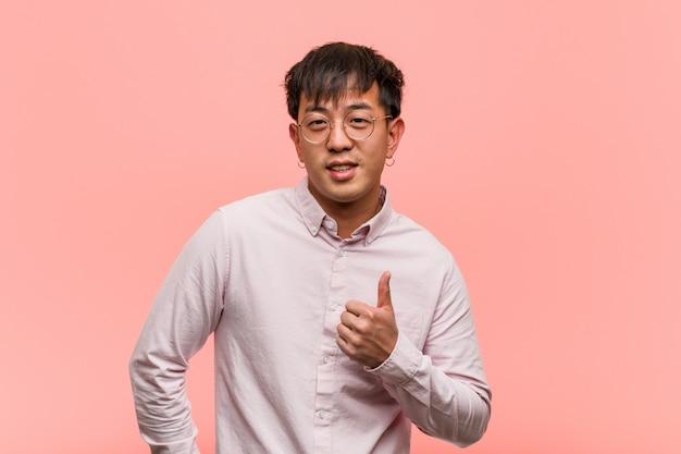 Junger chinesischer mann, der oben daumen lächelt und anhebt