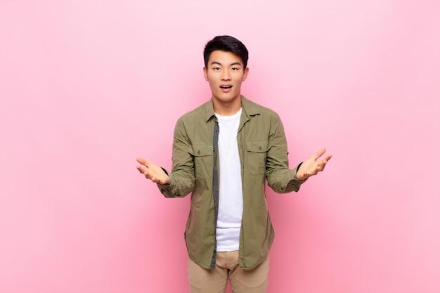 Junger chinesischer mann, der sich glücklich, erstaunt, glücklich und überrascht fühlt, als würde er ernsthaft omg sagen? unglaublich gegen flache farbwände