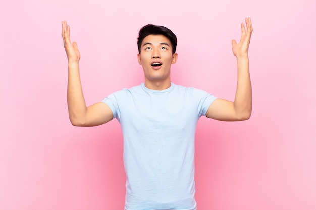 Junger chinesischer mann, der sich glücklich, erstaunt, glücklich und überrascht fühlt und den sieg mit beiden händen in der luft gegen flache farbwand feiert