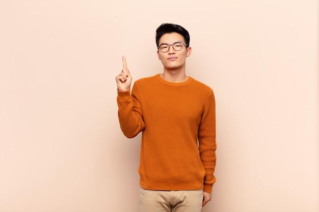 Junger chinesischer mann, der sich wie ein genie fühlt, das stolz finger in der luft hält, nachdem er eine große idee verwirklicht und eureka auf flacher farbwand sagt