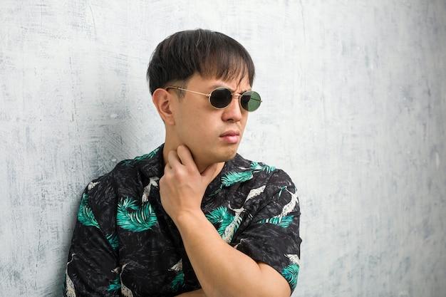 Junger chinesischer mann, der sommerausrüstung hustend trägt, krank wegen eines virus oder einer infektion