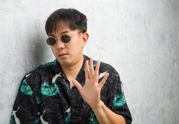 Junger chinesischer mann, der sommeroutfit trägt, lehnt etwas ab, das eine geste des ekels tut