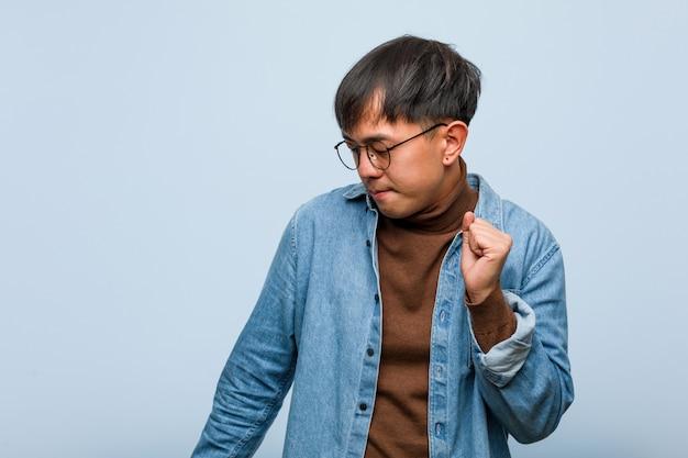 Junger chinesischer mann, der spaß tanzt und hat