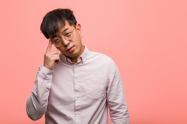 Junger chinesischer mann, der über eine idee nachdenkt