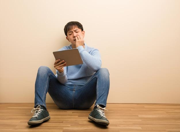 Junger chinesischer mann, der unter verwendung seiner beißenden nägel der tablette, nervös und sehr besorgt sitzt
