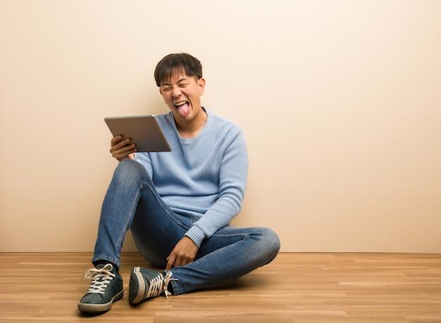 Junger chinesischer mann, der unter verwendung seiner funnny und freundlichen darstellenden zunge der tablette sitzt