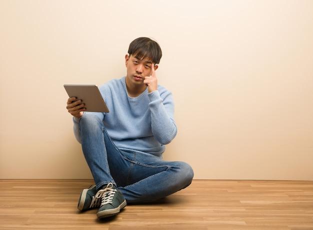 Junger chinesischer mann, der unter verwendung seiner tablette denkt an eine idee sitzt