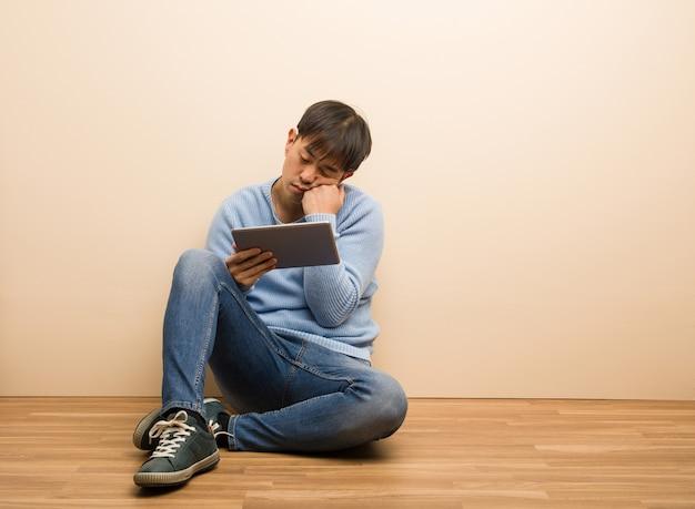 Junger chinesischer mann, der unter verwendung seiner tablette denkt an etwas, schauend zur seite sitzt