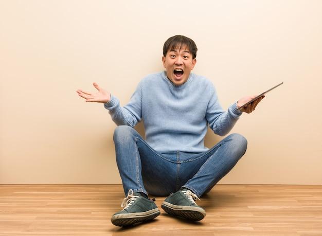 Junger chinesischer mann, der unter verwendung seiner tablette feiert einen sieg oder einen erfolg sitzt