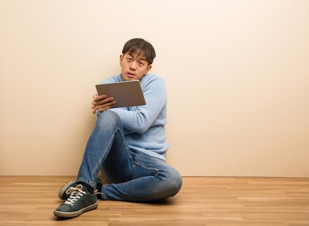 Junger chinesischer mann, der unter verwendung seiner tablette geht kalt wegen der niedrigen temperatur sitzt