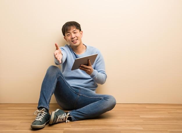 Junger chinesischer mann, der unter verwendung seiner tablette heraus erreicht sitzt, um jemand zu grüßen