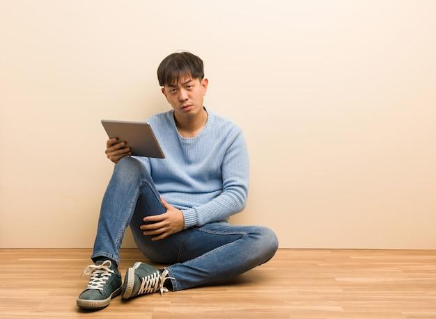 Junger chinesischer mann, der unter verwendung seiner tablette schilt jemand sitzt, das sehr verärgert ist