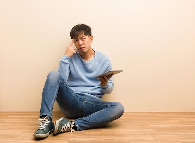 Junger chinesischer mann, der unter verwendung seiner tablette tut eine konzentrationsgeste sitzt