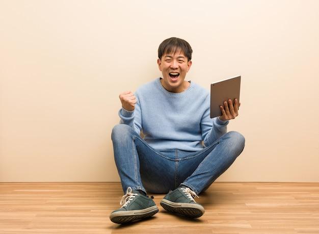 Junger chinesischer mann, der unter verwendung seiner tablette überrascht und entsetzt sitzt