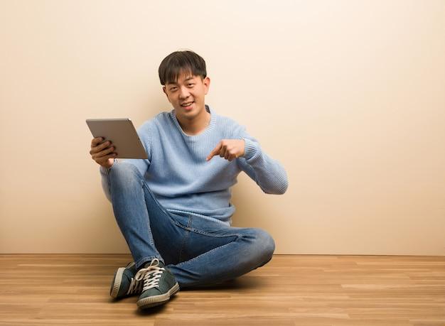 Junger chinesischer mann, der unter verwendung seiner tablette zeigt auf die unterseite mit den fingern sitzt