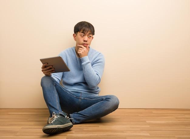 Junger chinesischer mann, der unter verwendung seiner tablette zweifelhaft und verwirrt sitzt