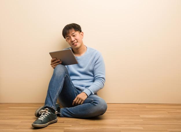 Junger chinesischer mann, der unter verwendung seiner tablettkreuzungsarme sitzt, lächelnd und entspannt