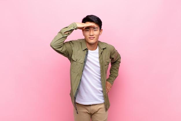 Junger chinesischer mann, der verwirrt und erstaunt schaut, mit der hand über stirn weit weg schauend, beobachtend oder suchend gegen flache farbwand