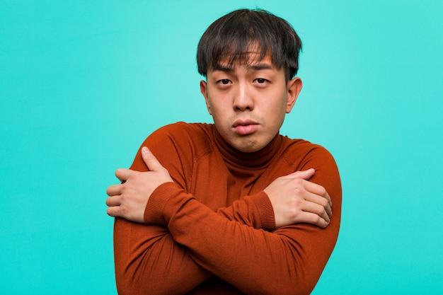 Junger chinesischer mann, der wegen der niedrigen temperatur kalt geht