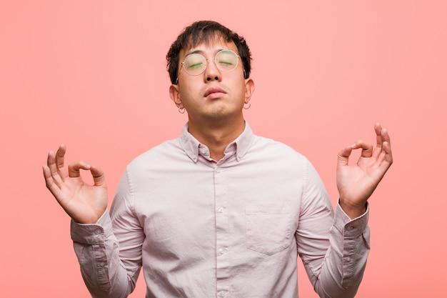 Junger chinesischer mann, der yoga durchführt