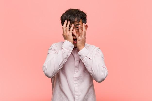Junger chinesischer mann fühlt sich besorgt und erschrocken