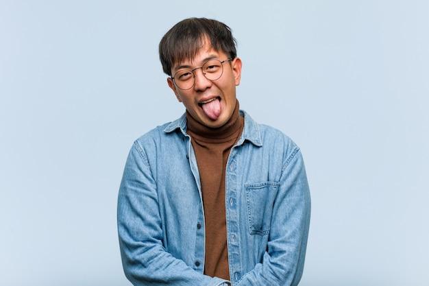 Junger chinesischer mann funnny und freundliche darstellende zunge