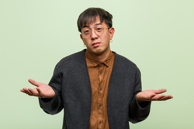 Junger chinesischer mann gegen eine grüne wand