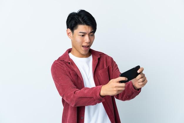Junger chinesischer mann lokalisiert auf weißem hintergrund, der mit dem handy spielt