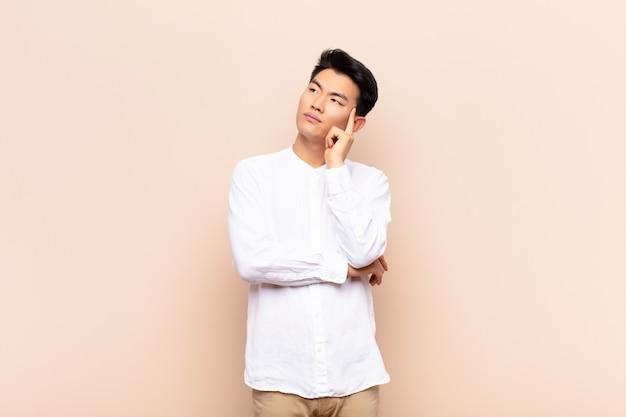 Junger chinesischer mann mit einem konzentrierten blick, der sich mit einem zweifelhaften ausdruck wundert und nach oben und zur seite gegen flache farbwand schaut