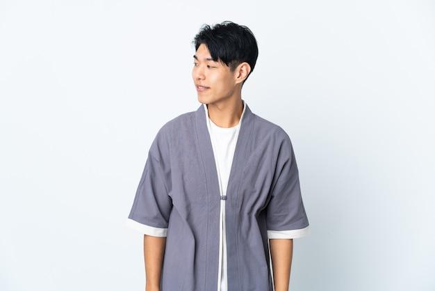 Junger chinesischer mann über isolierter wand, die zur seite schaut und lächelt