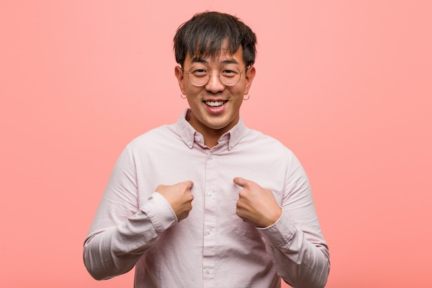 Junger chinesischer mann überrascht, fühlt sich erfolgreich und wohlhabend