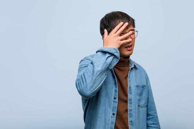 Junger chinesischer mann verlegen und gleichzeitig lachend
