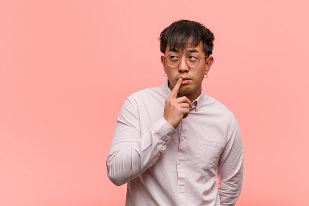 Junger chinesischer mann zweifelnd und verwirrt