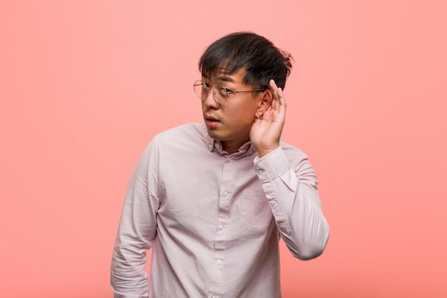 Junger chinesischer mannversuch zum hören eines klatsches