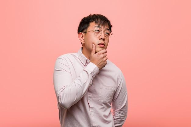Junger chinesischer zweifelnder und verwirrter mann
