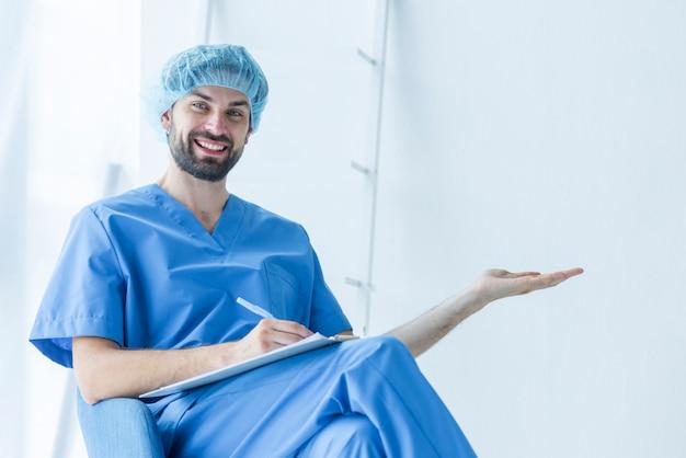 Junger chirurg mit dem klemmbrett, das leeren raum zeigt
